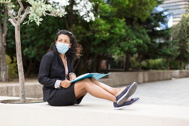 Junge lateinische studentin, die mit einem ordner auf der straße sitzt. als präventivmaßnahme gegen das covid-19-virus trägt sie eine medizinische maske.