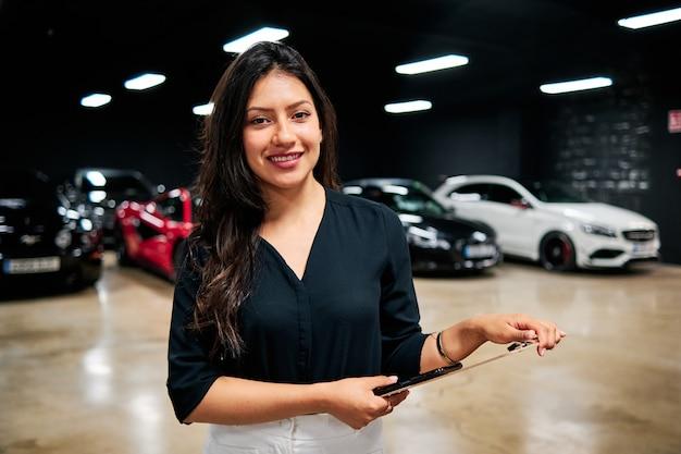 Junge lateinische verkäuferin, die luxusautos verkauft