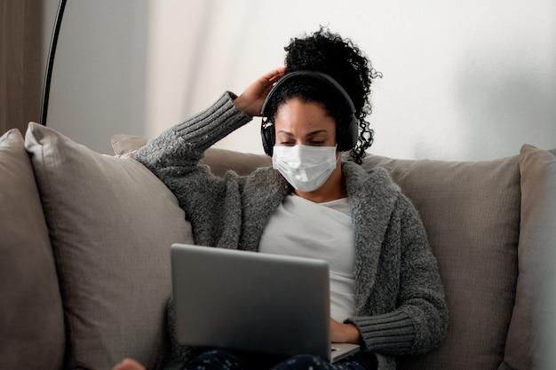 Junge latina-frau mit einer medizinischen maske, die während der coronavirus-pandemie von zu hause aus arbeitet