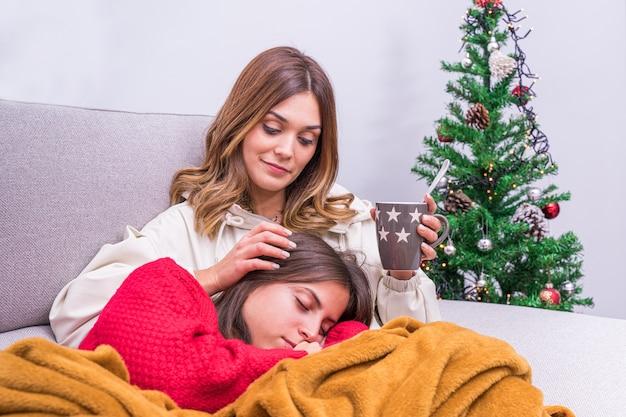 Junge lebianische frau, die kaffee trinkt, während sie ihren partner streichelt, während sie neben dem weihnachtsbaum schläft. konzept des lgbt-paares, der entspannung und des häuslichen lebens