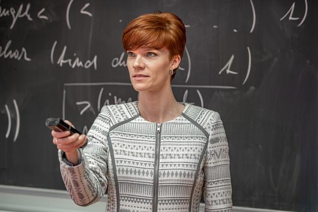 Junge lehrer vorlesungen an der school of mathematics, zeigt grafiken auf weißen platten