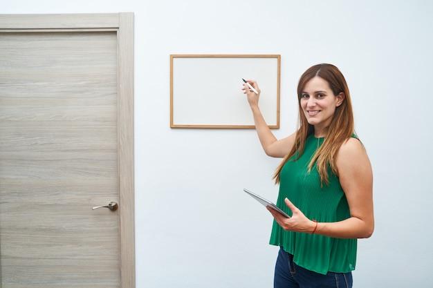 Junge lehrerfrau, die auf einem whiteboard schreibt. konzept des studiums, des unterrichts und des neuen kurses.