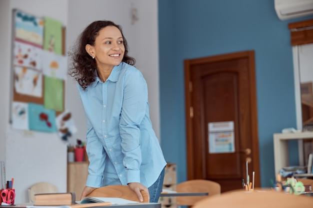 Junge lehrerin bereitet klassenzimmer für schüler vor