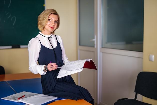 Junge lehrerin, die bei tisch im klassenzimmer arbeitet