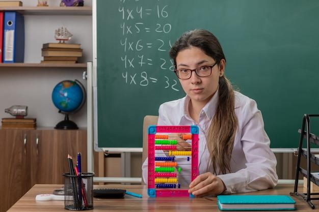 Junge lehrerin, die eine brille trägt, die an der schulbank mit rechnungen sitzt, die lektion vorbereiten, die zuversichtlich vor tafel im klassenzimmer schaut