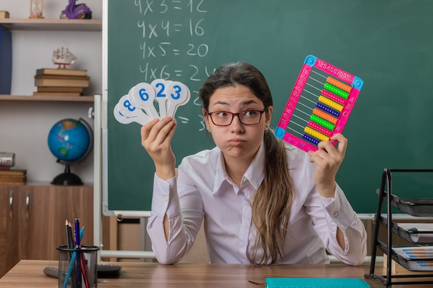 Junge lehrerin, die eine brille trägt, die an der schulbank mit rechnungen und nummernschildern sitzt, die müde und gelangweilt blasende wangen sehen, die lektion vor tafel im klassenzimmer erklären