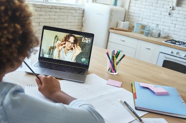 Junge lehrerin, die mit jugendlichem schulmädchen über video-chat-app kommuniziert, während sie online ist