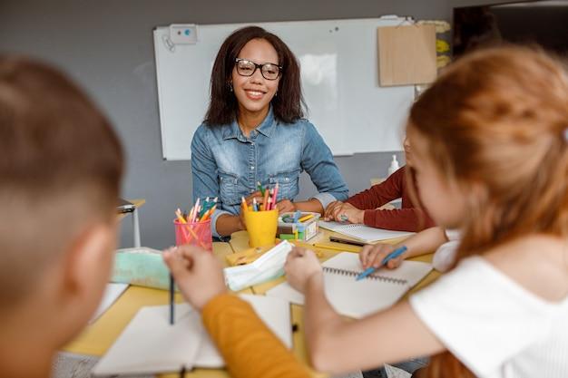 Junge lehrerin, die während des unterrichts im klassenzimmer mit kindern spricht