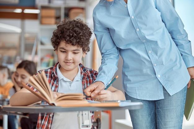 Junge lehrerin hilft, ihre schülerin zu lesen. grundschulkinder sitzen auf schreibtischen und lesen bücher im klassenzimmer.