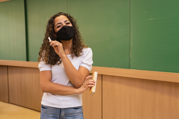 Junge lehrerin mit kreide und radiergummi in der hand, die eine chirurgische maske in neuer normalität trägt.