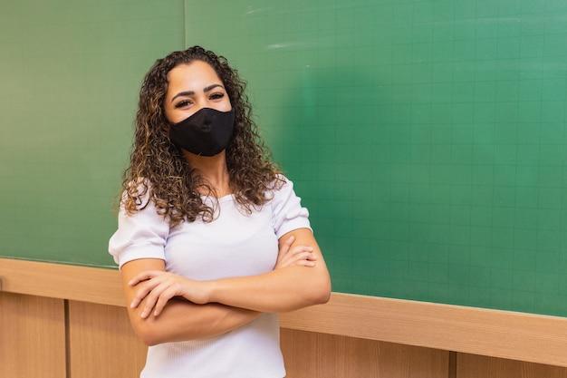 Junge lehrerin mit verschränkten armen im klassenzimmer mit tafel im hintergrund, die eine chirurgische maske in neuer normalität trägt. konzept des schulanfangs nach der pandemie