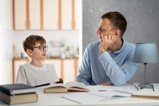 Junge lehrerin unterrichtet einen schüler zu hause. vater und sohn studieren schulfächer. häuslicher unterricht. fernunterricht.