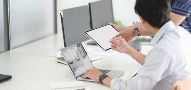 Junge leidenschaftliche ux-web-entwicklungsteam diskutieren smartphone-vorlage mit laptop