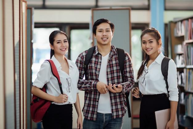 Junge lernende studenten, bibliotheksbücherregale