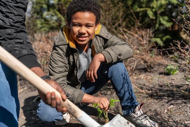 Junge lernt, wie man einen baum pflanzt