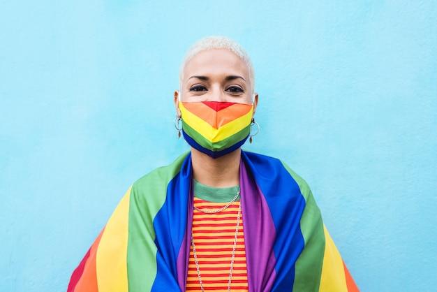 Junge lesbenfrau, die regenbogenmaske und flagge trägt - lgbt konzept