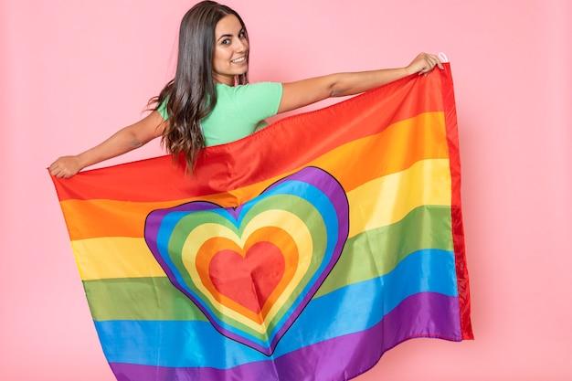 Junge lesbische frau des brunette glücklich und lächelnd mit regenbogen-homosexueller flagge des stolzes