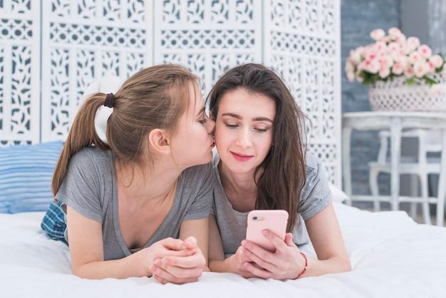 Junge lesbische frau, die auf dem bett küsst zum küken ihrer freundin unter verwendung des handys liegt