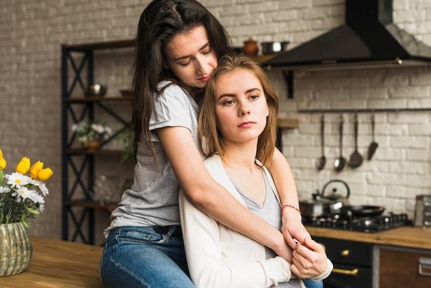 Junge lesbische frau, die ihre freundin steht in der küche liebt