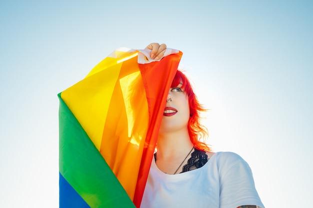 Junge lesbische frau mit der flagge des stolzes, die ihr auge bedeckt