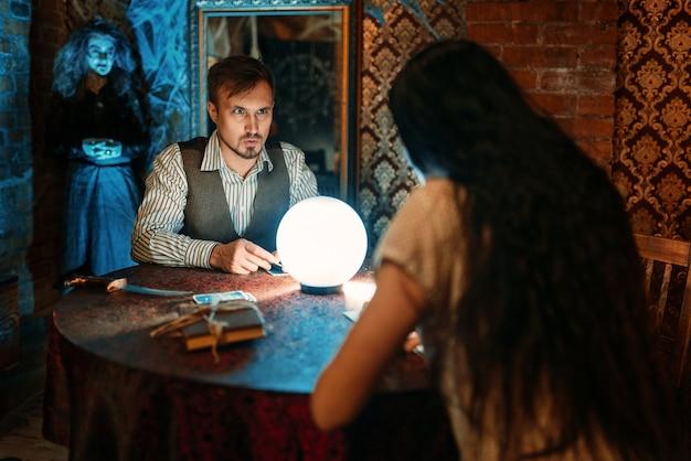Junge leute am tisch mit kristallkugel auf geistiger seance, gruselige hexe. weiblicher vorläufer ruft die geister
