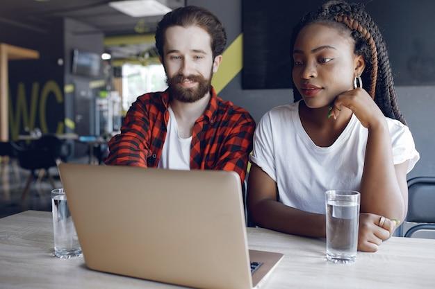 Junge leute arbeiten zusammen und benutzen den laptop