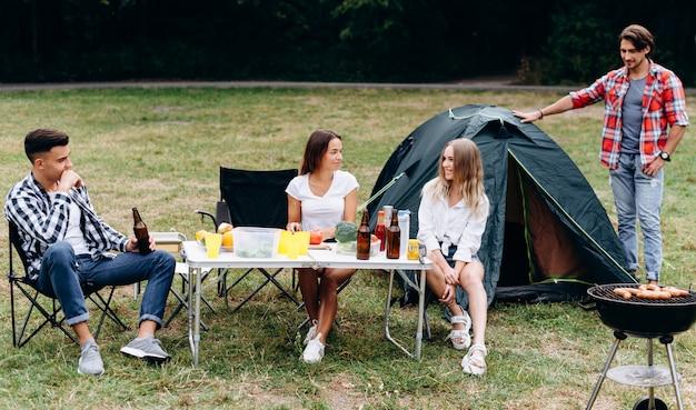 Junge leute auf dem campingplatz neben einem zelt essen zu mittag und haben eine lustige zeit