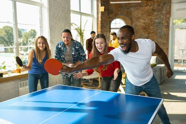 Junge leute, die am arbeitsplatz tischtennis spielen, spaß haben
