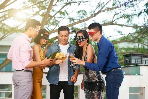 Junge leute, die an einer maskerade-party teilnehmen