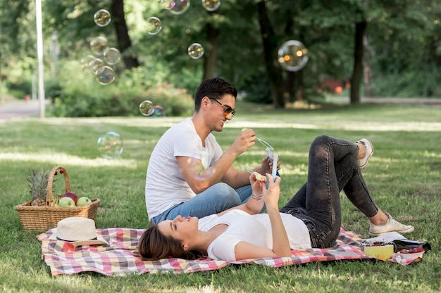 Junge leute, die auf einer decke am picknick stillstehen