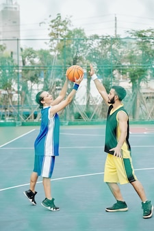 Junge leute, die basketball spielen