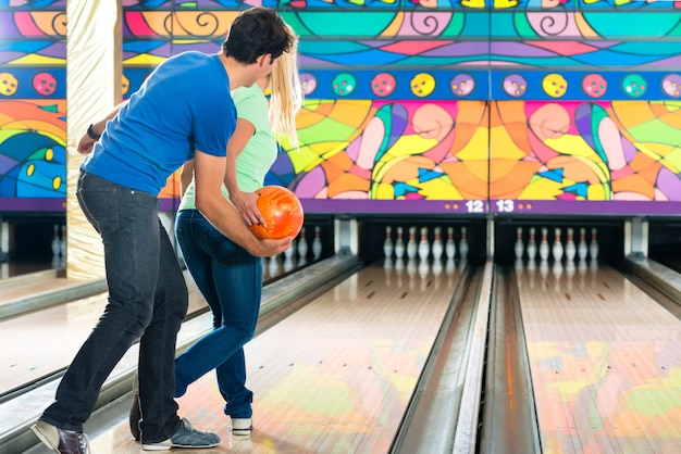 Junge leute, die bowling spielen und spaß haben