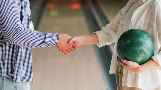 Junge leute, die bowlingkugeln halten