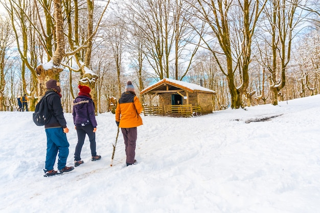 Junge leute, die den schneebedeckten naturpark oianleku in der stadt oiartzun besuchen, im winter neben penas de aya, gipuzkoa. baskenland
