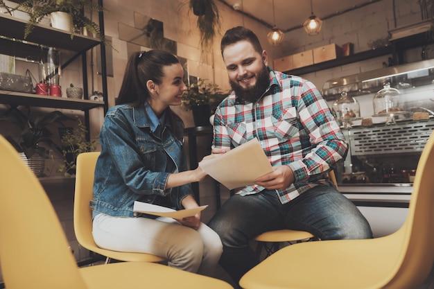 Junge leute, die dokumente während in einem café studieren