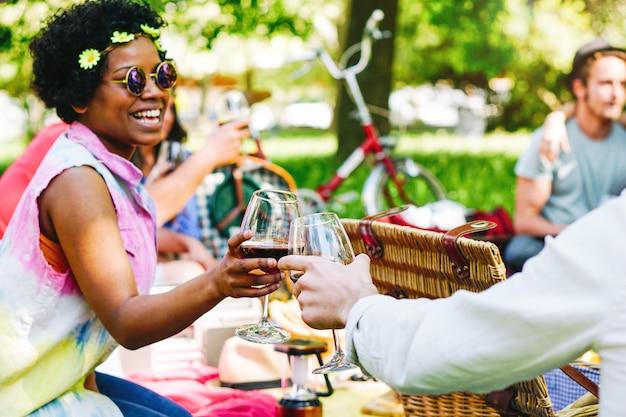 Junge leute, die ein wunderbares picknick in einem park haben und den freudigen moment des trinkens und essens genießen - glückliche freunde, die gläser wein rösten - afro-hipster-frau, die mit ihren freunden jubelt