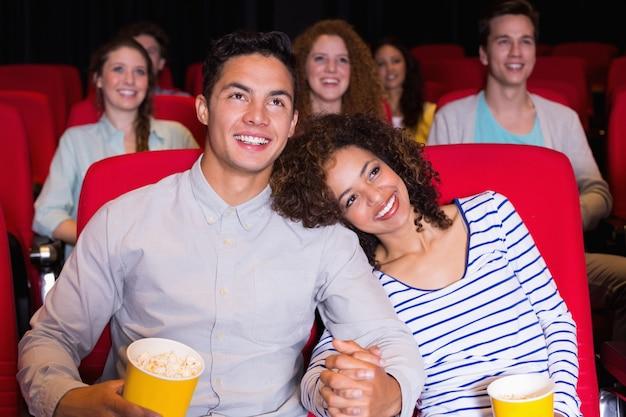 Junge leute, die einen film im kino aufpassen
