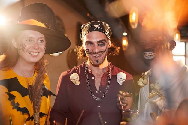 Junge leute, die halloween-kostüme im nachtclub tragen
