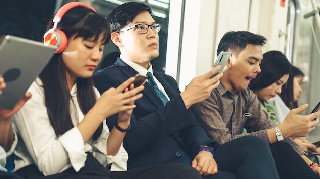 Junge leute, die handy in der öffentlichen u-bahn benutzen. urban city lifestyle und pendeln in asien konzept.
