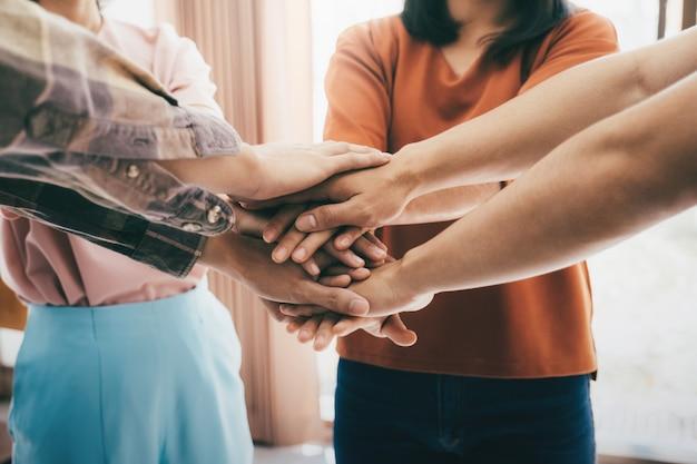 Junge leute, die ihre hände zusammen zeigen, die einheit und teamwork zeigen.