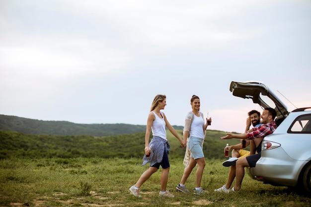 Junge leute, die im autotrank während der reise in der natur sitzen