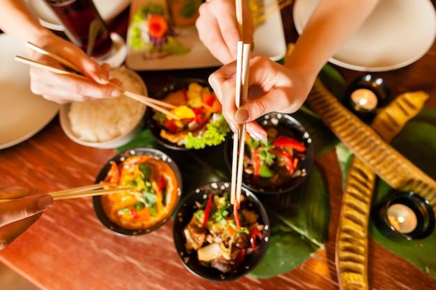 Junge leute, die im thailändischen restaurant essen