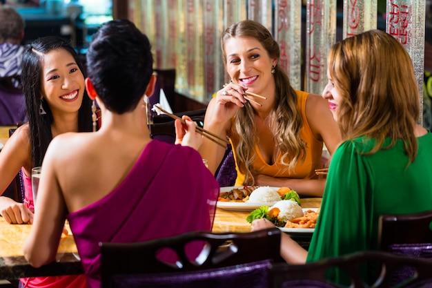Junge leute, die in asien-restaurant essen