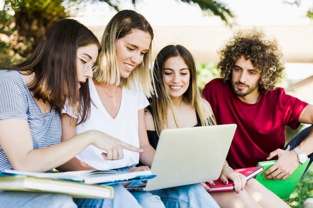 Junge leute, die laptop im park verwenden