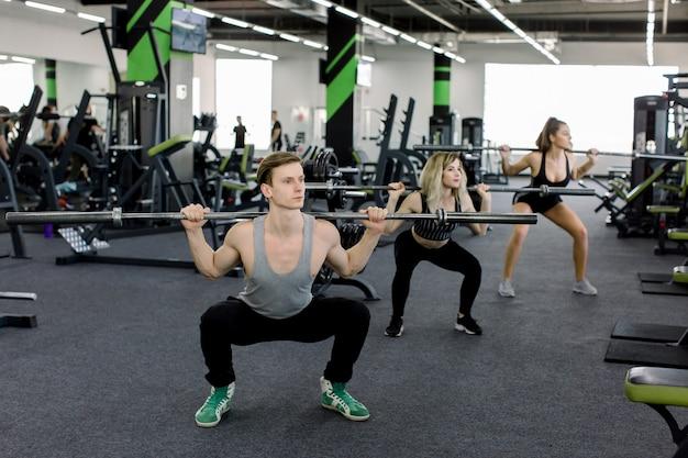 Junge leute, die mit hanteln im fitnessstudio trainieren. attraktive frauen und ein gutaussehender trainer für muskulöse männer trainieren im leichten modernen fitnessstudio. schönes mädchen hockt unter der aufsicht des trainers.