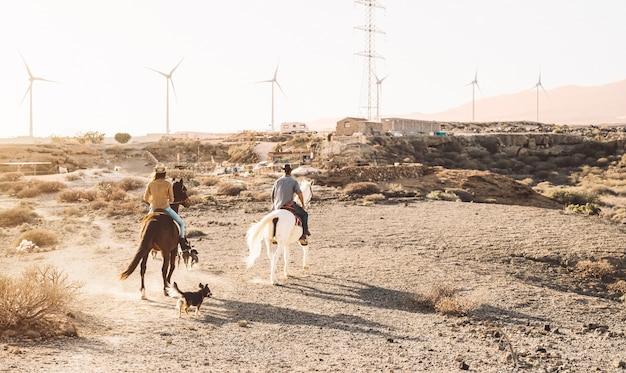 Junge leute, die pferde in der wüste reiten