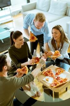 Junge leute, die pizza essen und apfelwein im modernen innenraum trinken