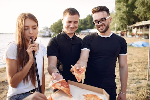 Junge leute, die pizza essen und shisha am strand rauchen
