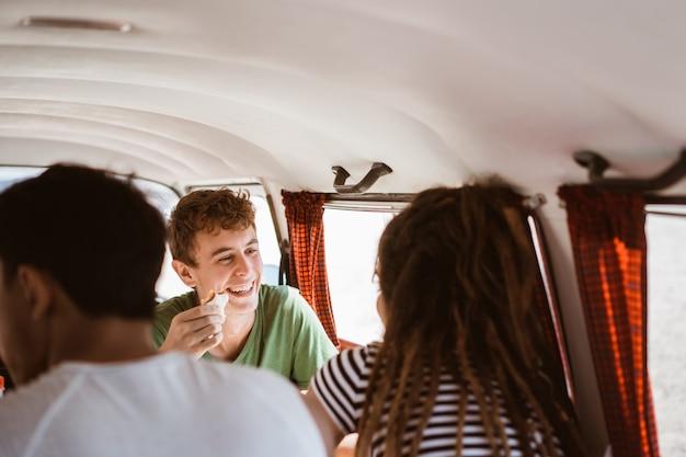 Junge leute, die sitzen, genießen ein sandwichfrühstück mit freunden