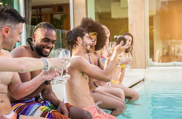 Junge leute, die spaß an den ferien in einem tropischen luxusresort lachen und haben